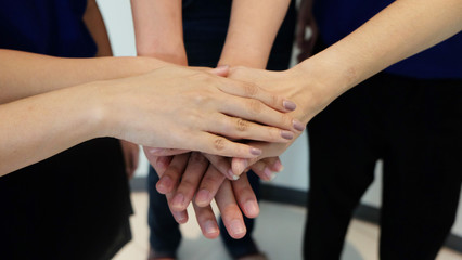 business team showing unity with putting their hands together. Close-Up of hands on top of each other