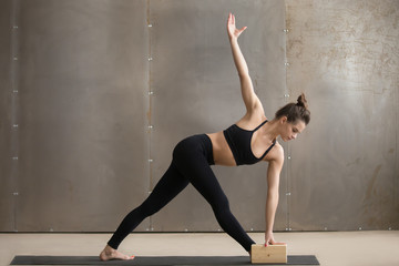Young attractive yogi woman in black practicing yoga, standing in Utthita Trikonasana exercise using block, extended triangle pose, working out, cool urban style, full length, grey studio background Wall mural