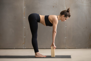 Young attractive yogi woman practicing yoga, standing in head to knees, Ardha uttanasana exercise, using block, Standing Half forward bend pose, working out, cool urban style, full length, grey studio Wall mural