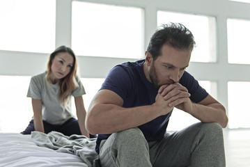 Depressed man sitting in bedroom