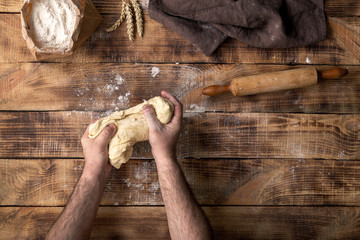 Wall Mural - Male hands knead the dough on a wooden table