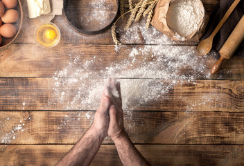Wall Mural - Man preparing bread dough on wooden table in bakery