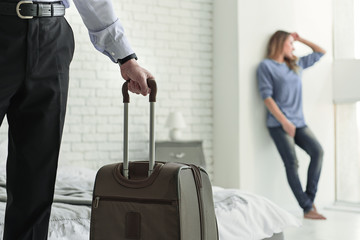 Man with baggage leaving his wife