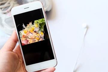 Hand hold smartphone tablet cell phone and vegetable salad photo for diet concept.