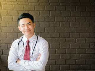 Asian handsome male doctor look good wearing a red tie and white shirt, tie and a listening heart smiled in a friendly engines.