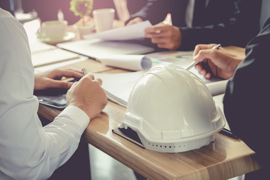 Architect and businessman planning meeting to work with commitment, set mind.Focus white safety helmets is foreground.