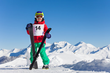 Portrait of happy kid boy holding skis in his hand