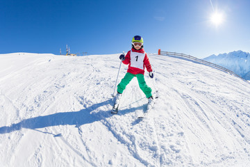 Little skier riding down a hill in alpine resort