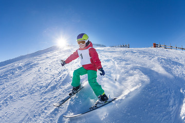 Active kid boy skiing in mountains at sunny day