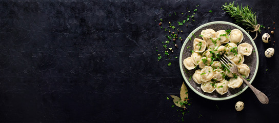 Traditional russian pelmeni, ravioli, dumplings with meat on black concrete background. Parsley, quail eggs, pepper, rosemary, bay leaf and spices. Top view. Copyspace. Banner.