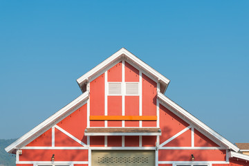 The beautiful gable roof of wooden red house with blue sky background