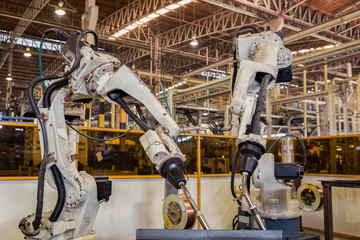 Team robot welding in teaching mode for new program in factory