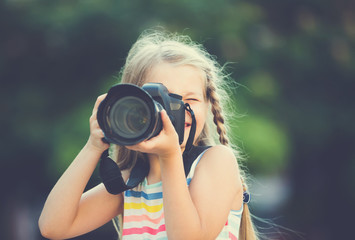 little girl with camera outdoors.
