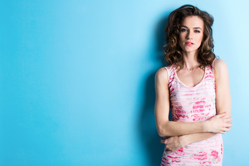 Studio portrait of a young beautiful woman in a pink dress against a blue wall background.