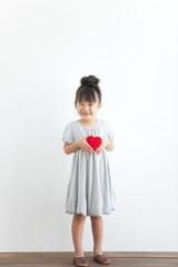 Portrait of girl holding red heart, white background