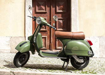 Green vintage motorcycle scooter staying on the cozy retro street in Lisbon, Portugal