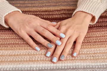 Fototapete - Beautiful blue manicure with rhinestones on knitted gradient background.