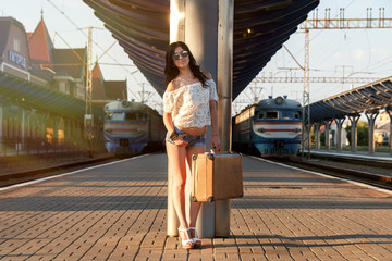 Lonely young brunette woman in sexy shorts with old suitcase on station platform with sunlight in sun glasses
