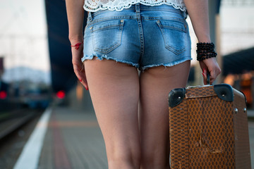 Female legs, in sexy shorts in shoes with an old suitcase on the station platform