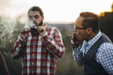 Friends smoking joint outdoors