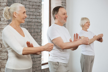 Three elderly people keeping hands in front of themselves