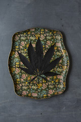 Cannabis leaf on a vintage flower patterned tray