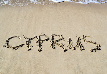 "The inscription ""Cyprus"" at the mesa of the sea shore. A sea wave with foam at the top of the frame."