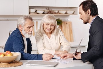 Confident real estate agent representing the house to aged couple