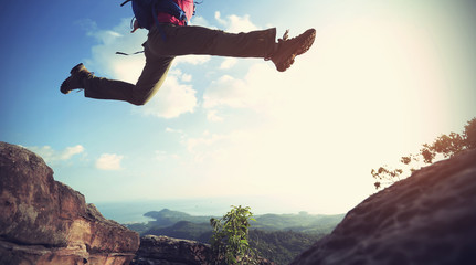 jumping over precipice between two rocky mountains . freedom, risk, challenge, success concept Wall mural