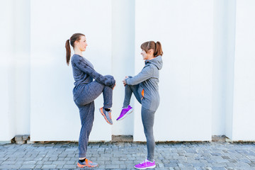 Two fit women standing in front of each other stretching her leg to warm up over white background
