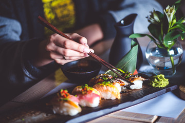 Photo sur Aluminium Sushi bar Man eating sushi set with chopsticks on restaurant