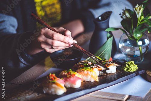 man eating sushi set with chopsticks on restaurant stockfotos und lizenzfreie bilder auf. Black Bedroom Furniture Sets. Home Design Ideas