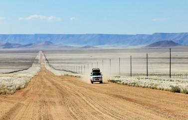 Pickup truck driving fast on long straight desert road