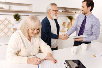 Retired woman signing contract while her husband greeting the notary