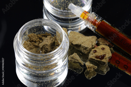 Close up of hash chunks with hash oil syringe over black background