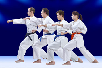 Sportsmen with different colors of belts are training punch arm