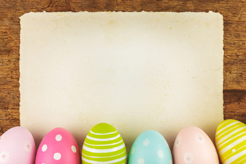 Colorful painted easter eggs with blank paper sheet