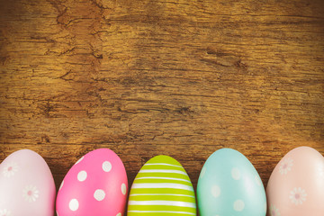 Colorful easter eggs in front of an old wooden background