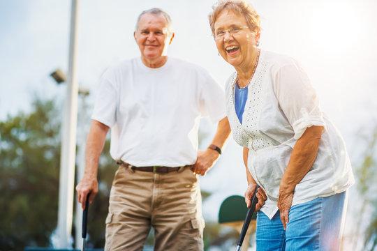 happy seniors playing mini golf