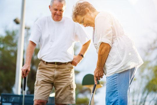 retired lifestyle of senior couple playing mini golf