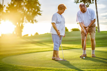 active senior lifestyle, elderly couple playing golf together at sunset Wall mural