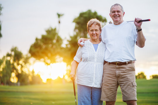portrait of happy senior couple playing golf enjoying retirement