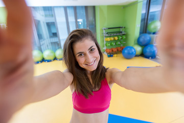 sport woman smile at camera self picture at gym, young girl picture herself exercising fitness center