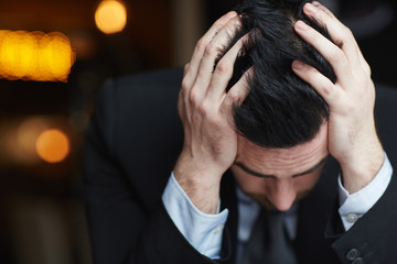 Portrait of modern businessman clasping head with hands, fighting stress and exhaustion against black background