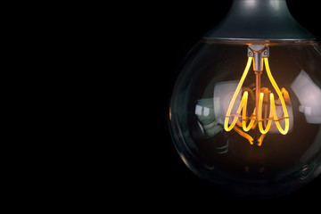 retro vintage light bulb with led technology bult-in on warm light yellow tint and black background, energy saving with old style atmosphere