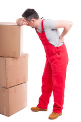 Full body of man having a back pain leaning on boxes