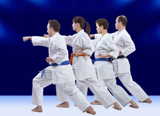 Adult athletes in karategi are training punch arm