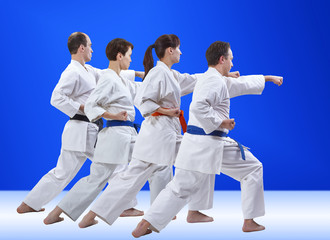 Four adult athletes are training punch on a light blue background