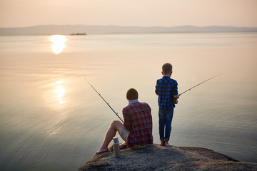 Wall Murals Fishing Back view portrait of adult man and teenage boy sitting together on rocks fishing with rods in calm waters with landscape of setting sun, both wearing checkered shirts
