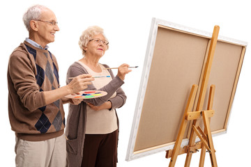 Elderly man and woman painting on a canvas with paintbrushes